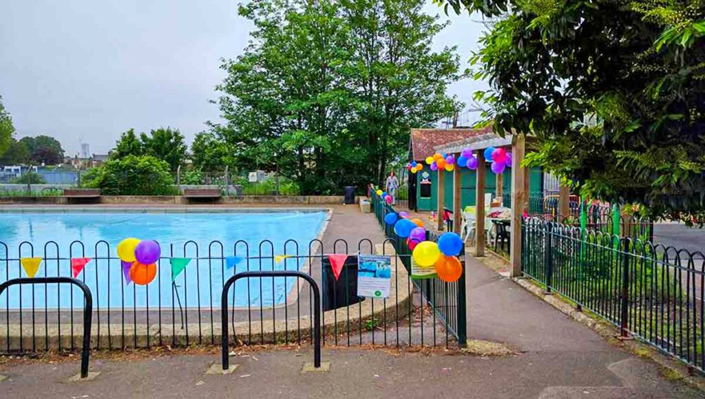 paddling pool with balloons on fence