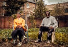 two gardeners sitting in front of vegetable patch