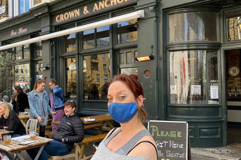 woman Coid mask outside pub