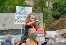 girl on man's shoulders at protest rally