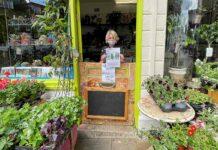 shopkeeper at door of shop