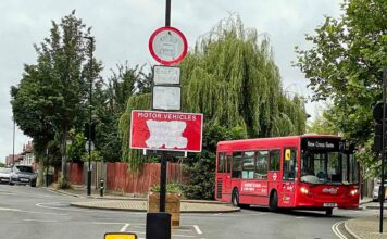 vandalised traffic sign with bus in background