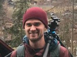 portrait of man outdoors in beanie with camera tripod