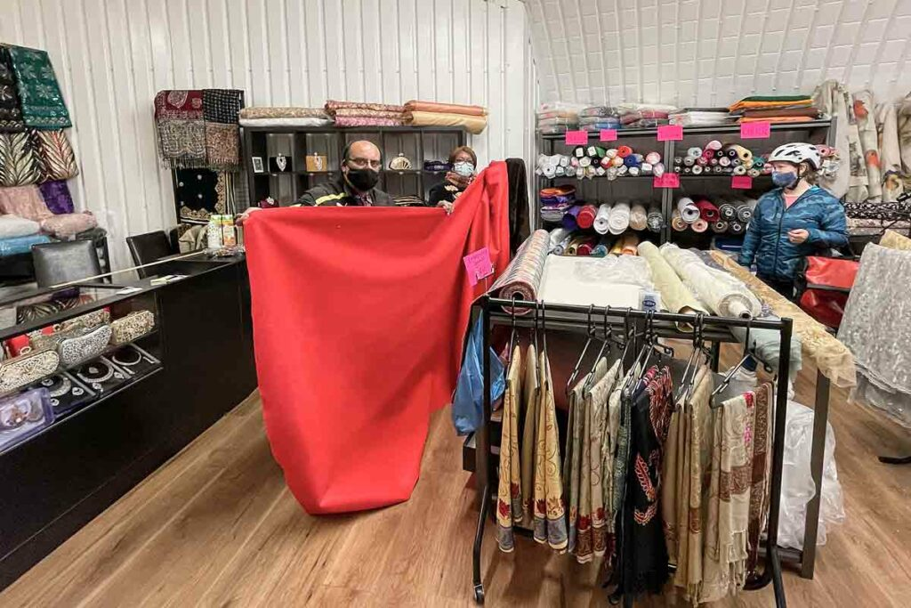 shopkeeper displays cloth