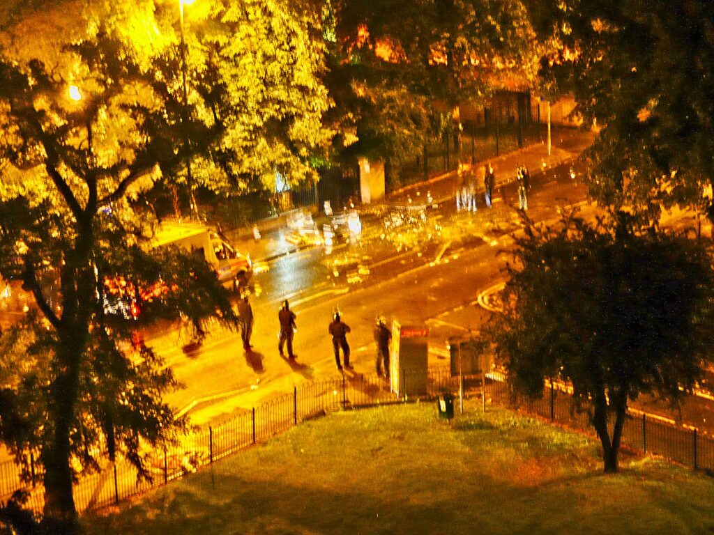 nighttime riot scene with police presence