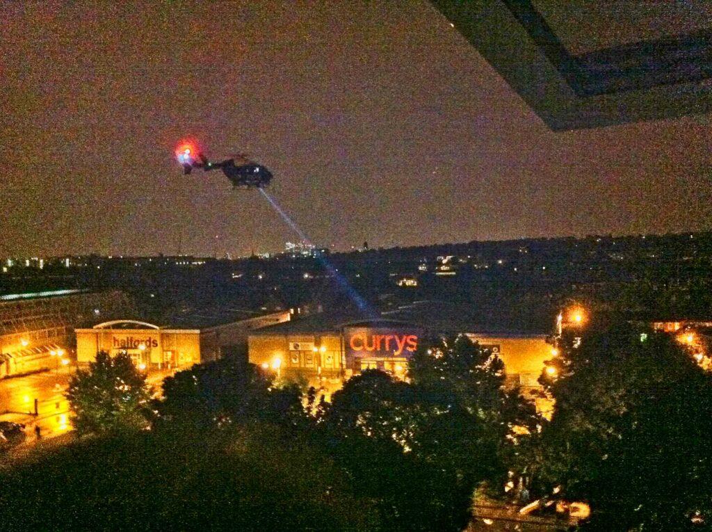 police helicopter using spotlight over riot scene