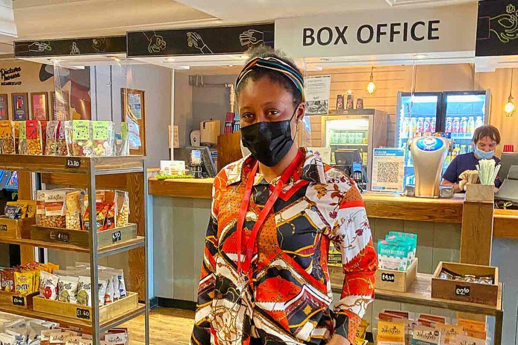 woman in covid mask in cinema foyer