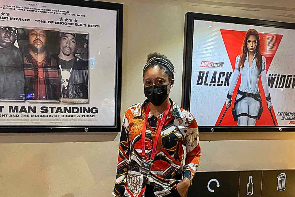 woman in covid mask in front od movie posters