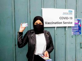 woman at vaccination centre displays vaccine record card