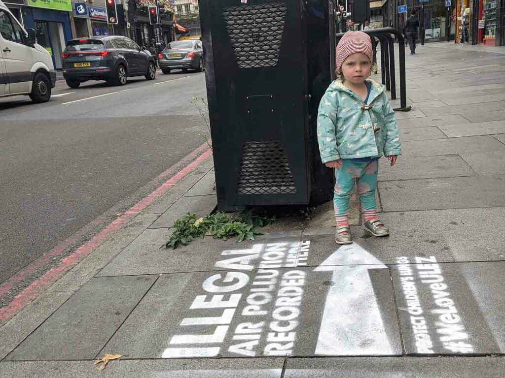 young girl with pavement stencil slogan