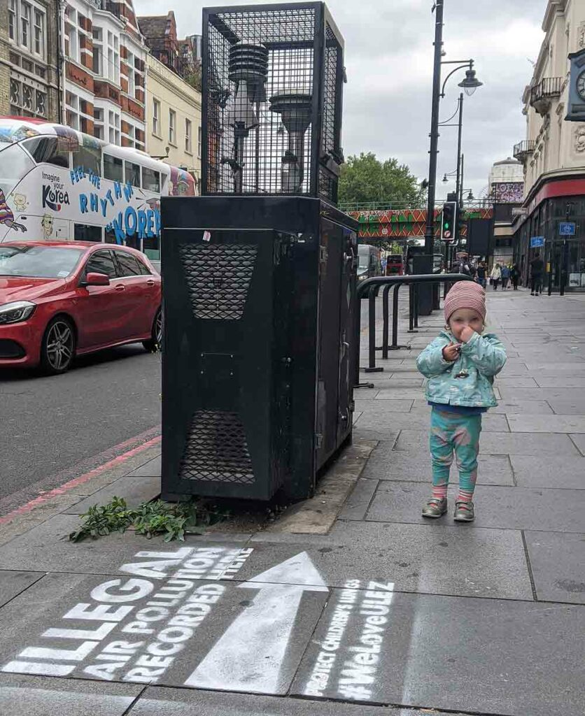 girl next to street pollution monitor