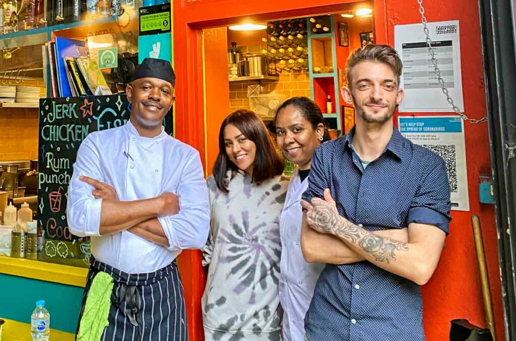 chef and servers at door of restaurant