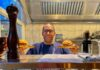 chef at servers hatch with burger