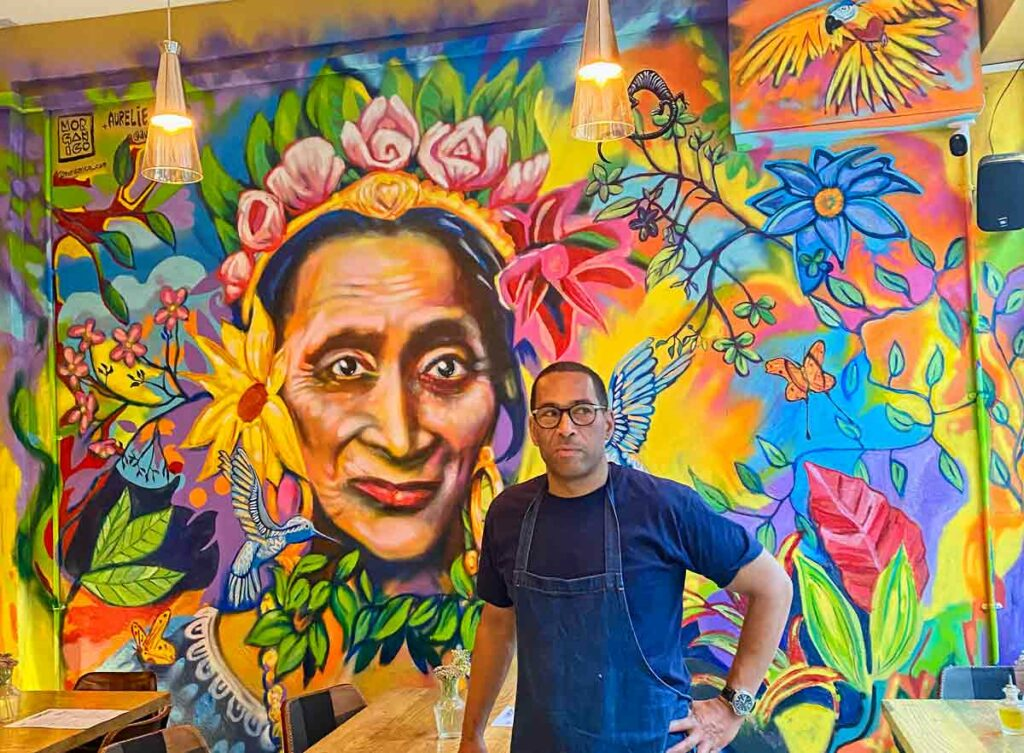 man in front of wall painting